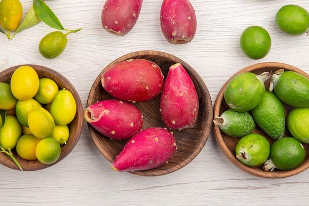 Vista dall'alto diversi frutti freschi all'interno di piatti su sfondo bianco dieta tropicale esotica colore vita sana