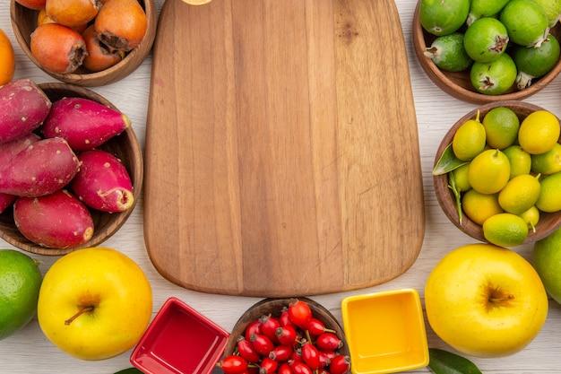 Vista dall'alto diversi frutti freschi all'interno di piatti sullo sfondo bianco colore tropicale maturo dieta dolce vita sana esotica