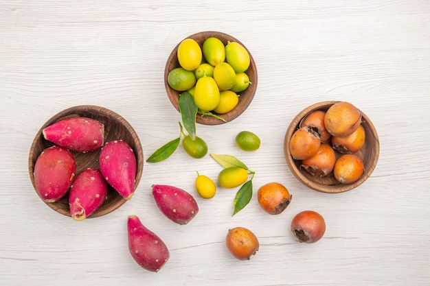 Top view different fresh fruits inside plates on white desk fruit tropical ripe diet exotic color