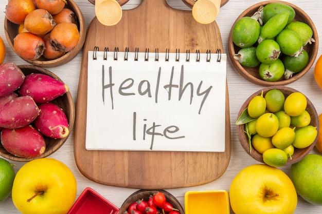 Вид сверху различных свежих фруктов внутри тарелок с надписью здорового образа жизни на белом фоне тропических спелых цветов, диета, мягкая экзотика