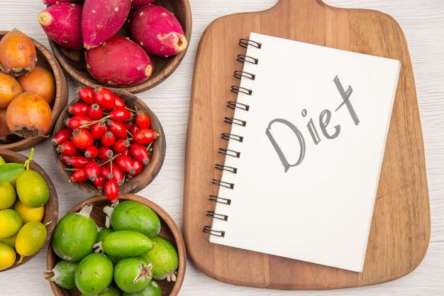 Вид сверху разных свежих фруктов внутри тарелок с блокнотом на белом фоне, цвет тропического здоровья, экзотические ягодные деревья, спелая диета