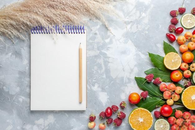 明るい白い机の上のメモ帳でさまざまな新鮮な果物の上面図果物新鮮なまろやかな熟した