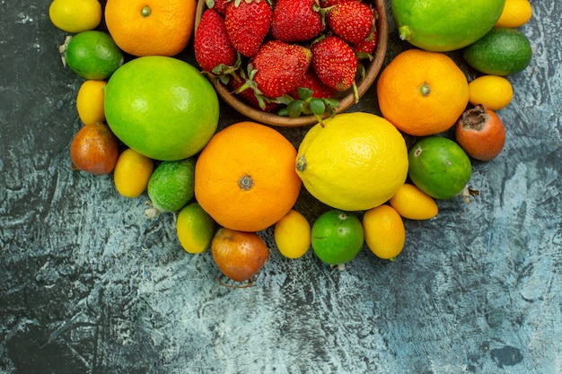 Top view different fresh fruits with red strawberries on grey background