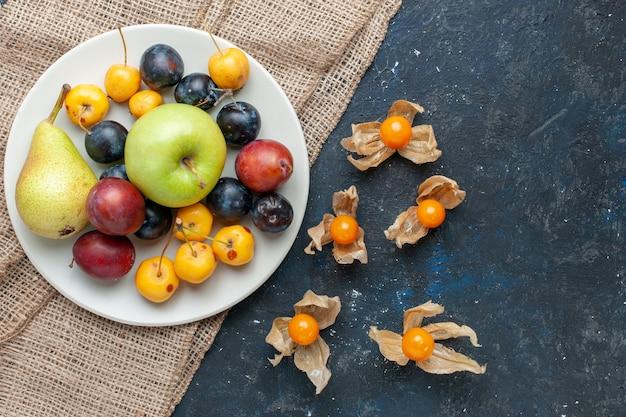 Vista dall'alto di diversi freschi frutis pera prugne prugnoli e mela all'interno della piastra sulla scrivania scura, frutta cibo fresco snack salute vitamina