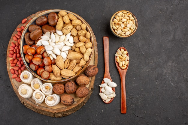 Top view of different fresh nuts on dark surface