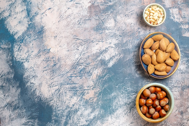 Top view of different fresh nuts on light blue surface