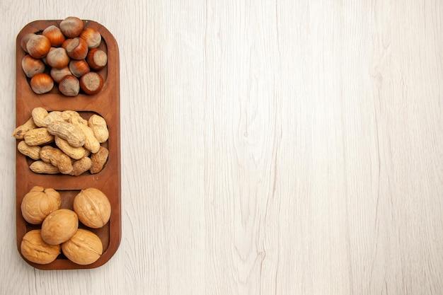 上面図さまざまな新鮮なナッツピーナッツヘーゼルナッツと白い机の上のクルミナッツスナック多くの植物