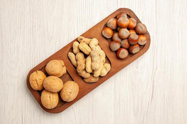Вид сверху различных свежих орехов, арахиса, фундуков и грецких орехов на белой столовой ореховой закуске на многих растениях