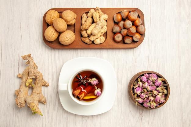 上面図さまざまな新鮮なナッツピーナッツヘーゼルナッツとクルミと白い机の上のお茶ナッツスナック多くの植物