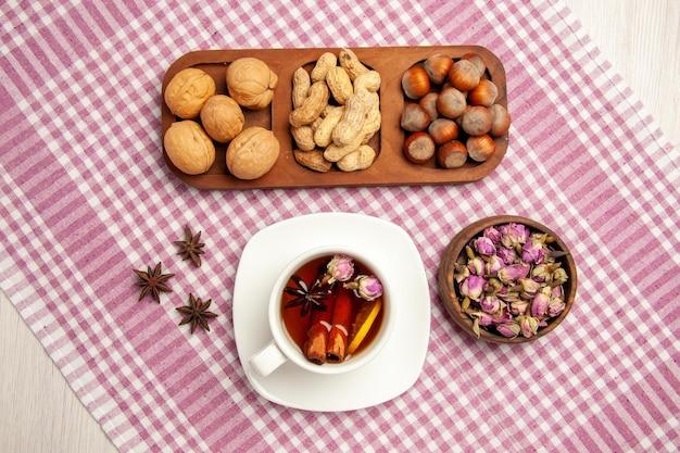 上面図さまざまな新鮮なナッツピーナッツヘーゼルナッツとクルミと白い机の上のお茶ナッツスナック多くの植物茶