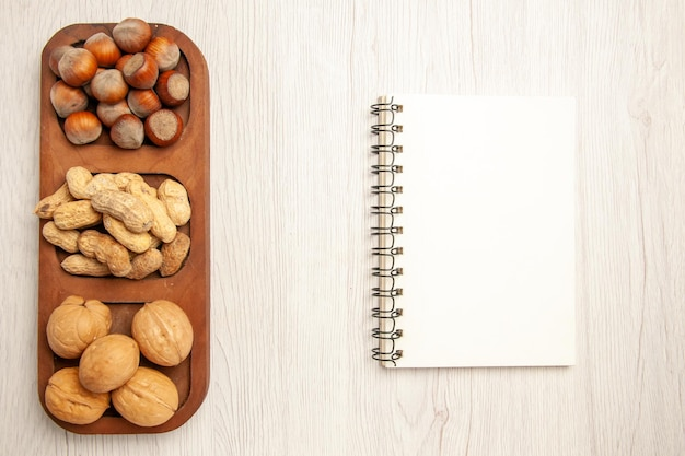 Top view different fresh nuts peanuts hazelnuts and walnuts on the white desk nut snack many plant
