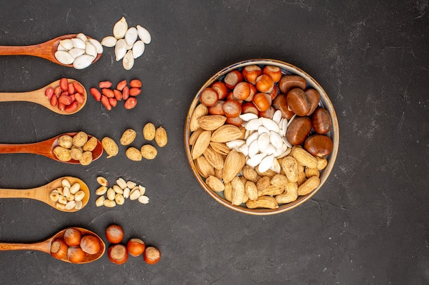 Top view of different fresh nuts peanuts and other nuts on dark grey surface