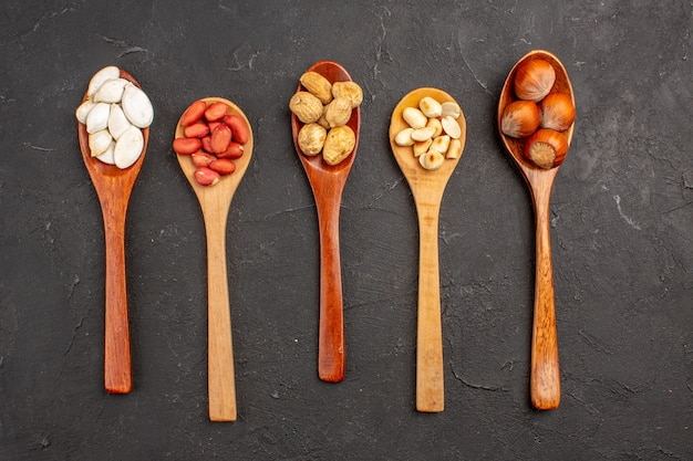 Top view of different fresh nuts peanuts and other nuts on spoons on dark surface