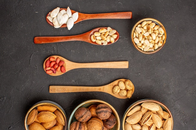 Top view of different fresh nuts with confitures on dark surface