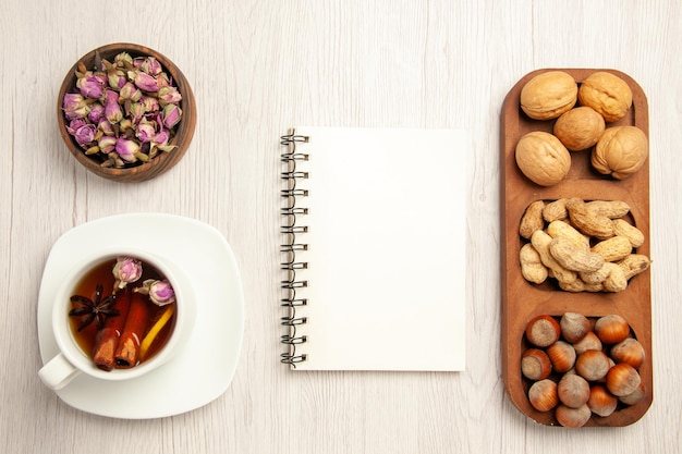 Top view different fresh nuts with cup of tea on a white desk nut snack many plant tea