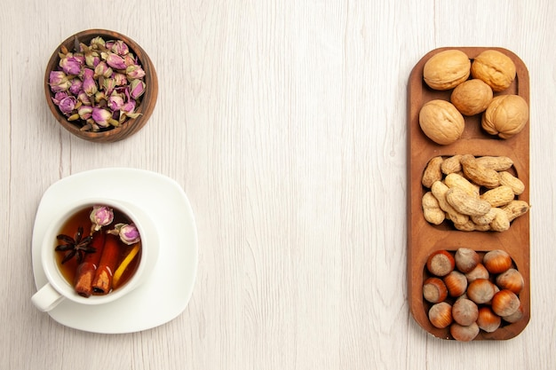 Top view different fresh nuts with cup of tea on white desk nut snack many plant tea
