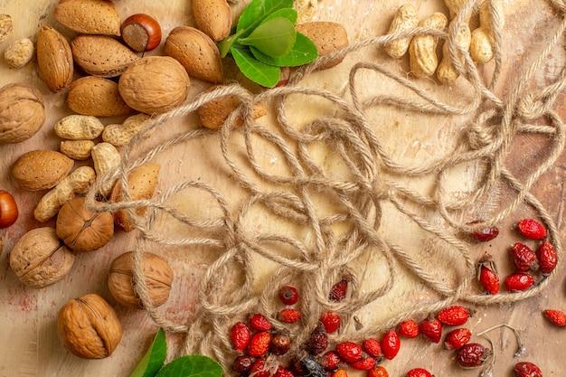 上面図木製デスクナットピーナッツクルミにロープでさまざまな新鮮なナッツ