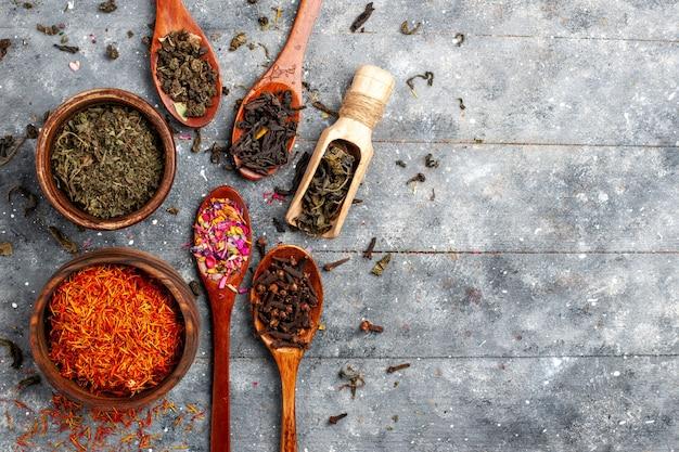 Vista dall'alto diversi gusti secchi di tè fresco sul pavimento grigio pianta da frutto del tè sapore di fiori