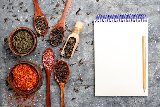 灰色の机の上のさまざまな新鮮なお茶の乾燥フレーバーの上面図