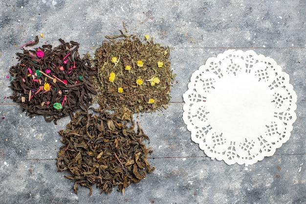 灰色の素朴な机の上のさまざまな新鮮なお茶の乾燥フレーバーの上面図