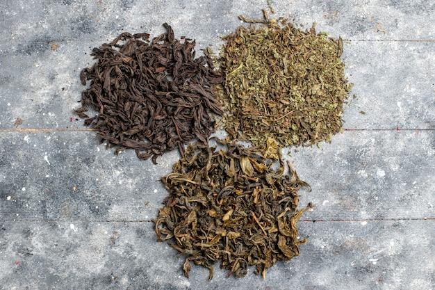 灰色の机の上で乾燥した別の新鮮なお茶の上面図