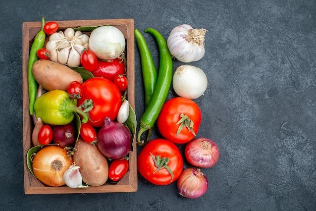 Вид сверху разные свежие овощи на темном столе, салат, свежие спелые овощи