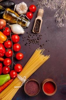 어두운 공간에서 이탈리아 파스타와 조미료와 함께 다른 신선한 야채를 봅니다.