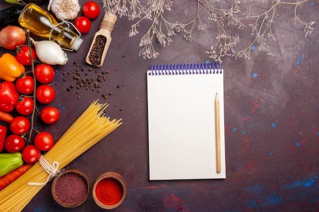 暗い空間でイタリアンパスタと調味料とさまざまな新鮮な野菜の上面図