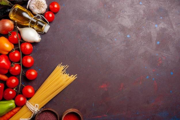 Vista dall'alto diverse verdure fresche con pasta italiana su uno spazio buio