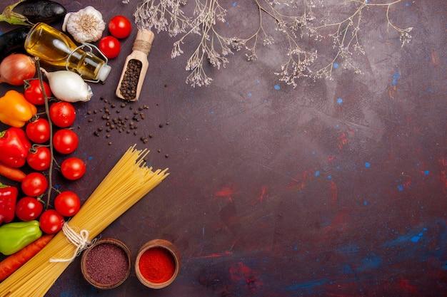 Вид сверху разных свежих овощей с итальянской пастой на темном пространстве