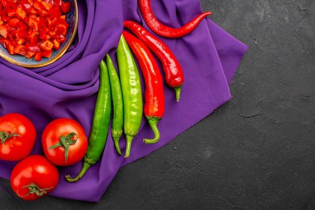 Вид сверху разных свежих овощей с нарезанным перцем на темном столе, спелых салатах