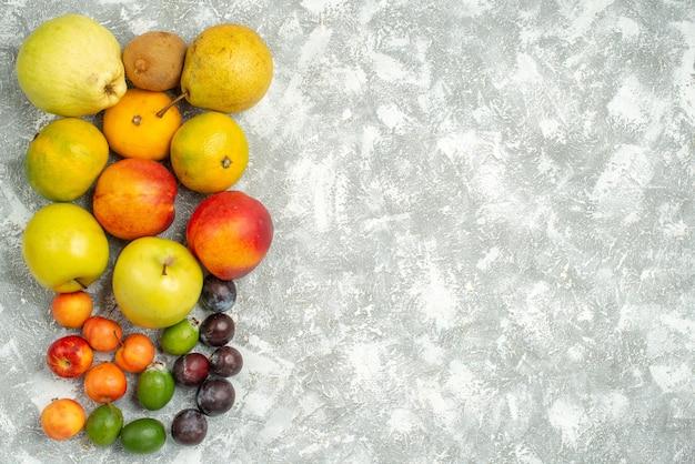 Вид сверху разные фруктовые композиции свежие фрукты на белом фоне дерево витамин свежий цвет спелые плоды