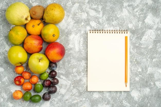 Вид сверху разные фруктовые композиции свежие фрукты на белом фоне дерево витамин свежие цвета спелые фрукты