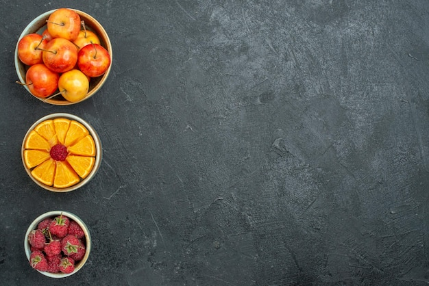 Top view different fruit composition inside little pots on dark background fresh fruits mellow health ripe