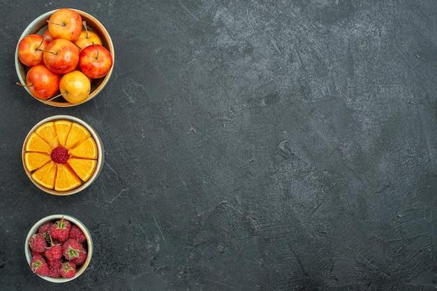 暗い背景の小さな鉢の中のさまざまな果物の組成の上面図新鮮な果物まろやかな健康熟した