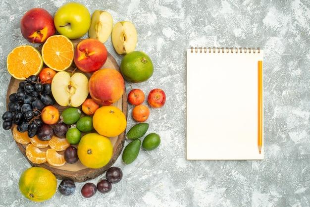 上面図白い背景の木にスライスされた新鮮な果物全体のさまざまな果物の組成