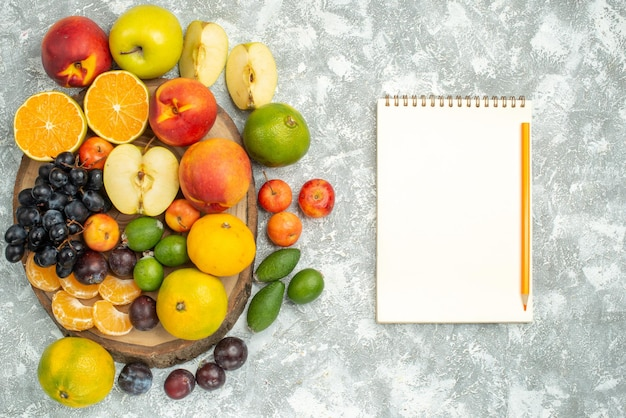 Top view different fruit composition sliced and whole fresh fruits on white background tree vitamine ripe fruits mellow color