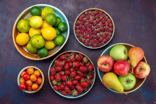 暗い机の上のさまざまなフルーツベリーと柑橘類の上面図柑橘類の熱帯のエキゾチックなオレンジ色の果物