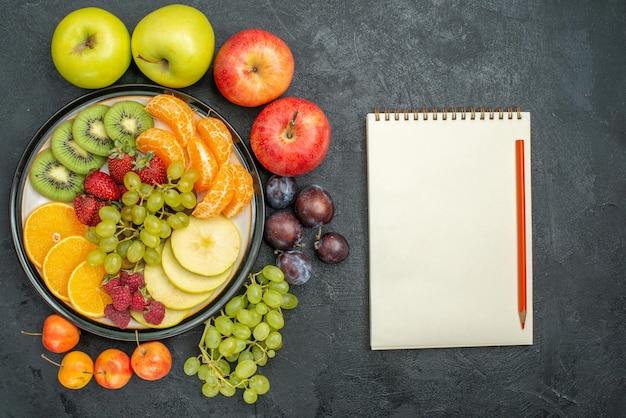 上面図さまざまな果物の組成が新鮮で、暗い背景に熟しているまろやかな新鮮な果物の健康が熟している