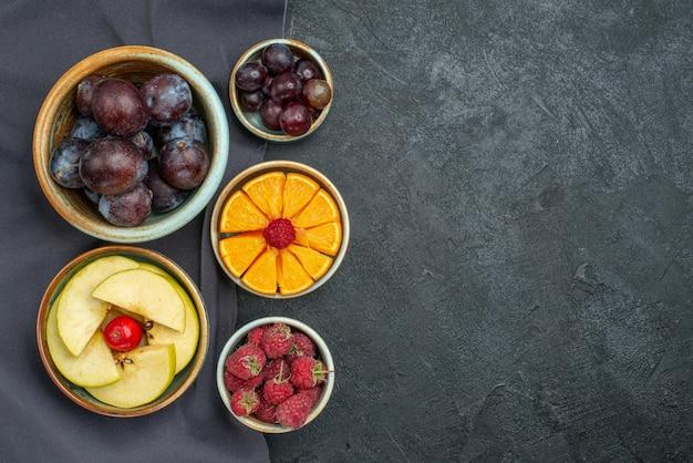 Вид сверху разные композиции фруктов свежие и спелые на темно-сером столе спелые фрукты здоровое растение спелого цвета