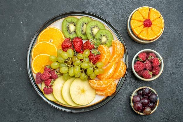 上面図さまざまな果物の組成暗い背景の新鮮なスライスされた果物健康新鮮な果物まろやかな熟した