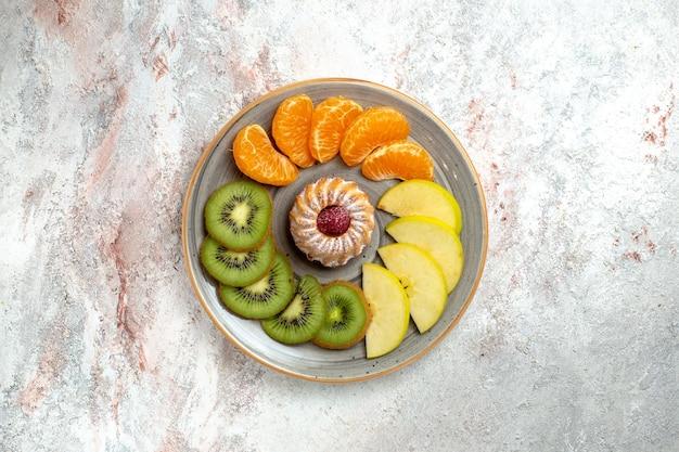 Вид сверху разные фруктовые композиции свежие и нарезанные фрукты на белом фоне спелые фрукты спелого цвета здоровья
