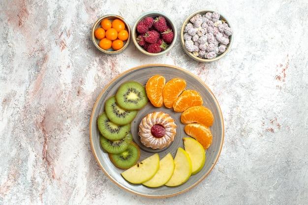 上面図さまざまな果物の組成新鮮なスライスされた果物と白い机の上のケーキまろやかな果物健康熟したビタミン