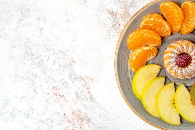 上面図さまざまな果物の組成新鮮なスライスされた果物と白い机の上のケーキまろやかな熟した果物の色の健康