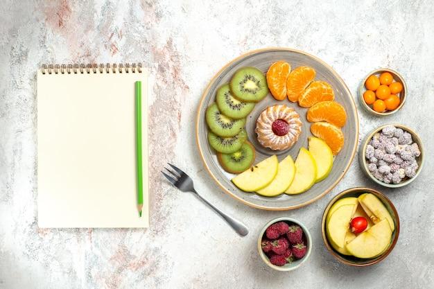 上面図さまざまな果物の組成白い背景に小さなケーキと新鮮な果物まろやかな果物ビタミン健康熟した