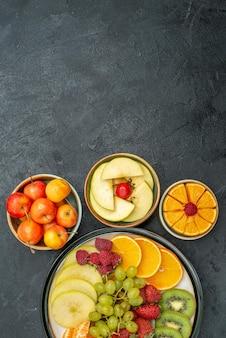 上面図さまざまな果物の組成新鮮なまろやかでスライスされた果物暗い机の上で新鮮な果物まろやかな健康熟した
