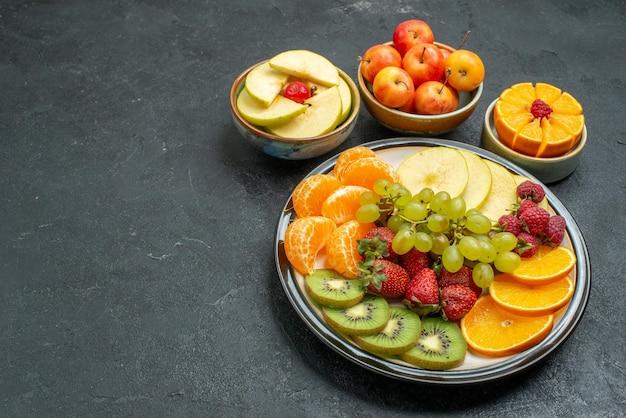 Vista dall'alto composizione di frutta diversa frutta fresca dolce e affettata sullo sfondo scuro frutta fresca dolce salute matura