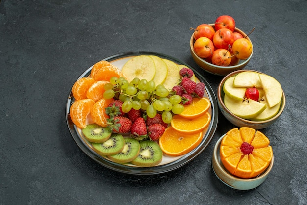 Top view different fruits composition fresh mellow and sliced fruits on dark background fresh fruits mellow health