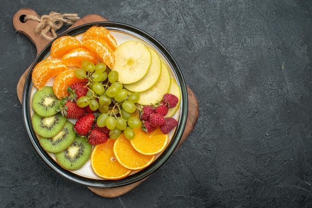 Вид сверху различных фруктов состав свежих нарезанных и спелых на сером фоне спелых свежих фруктов здоровья спелых
