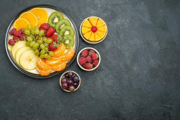 Vista dall'alto composizione di frutta diversa frutta fresca e affettata sullo sfondo scuro frutti freschi e dolci maturi